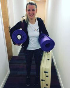 Pilates Adel instructor. Laura Hebden. Girl with blond hair holding pilates mat